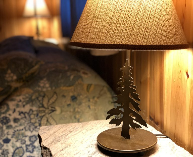 metal lamp shaped like a pine tree on a bedside table