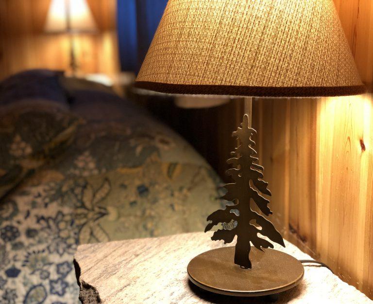 metal lamp shaped like a pine tree on a bedside table