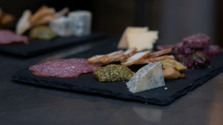 close up of salami, mustard, crackers and various cheeses on slate server tray