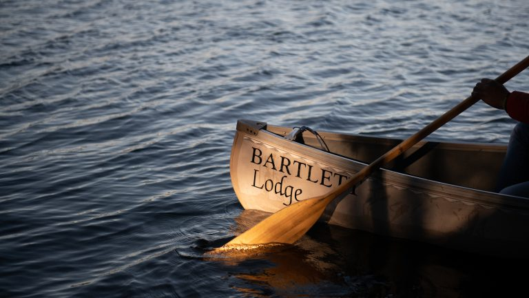 front end of a Bartlett Lodge canoe with a paddle in the water