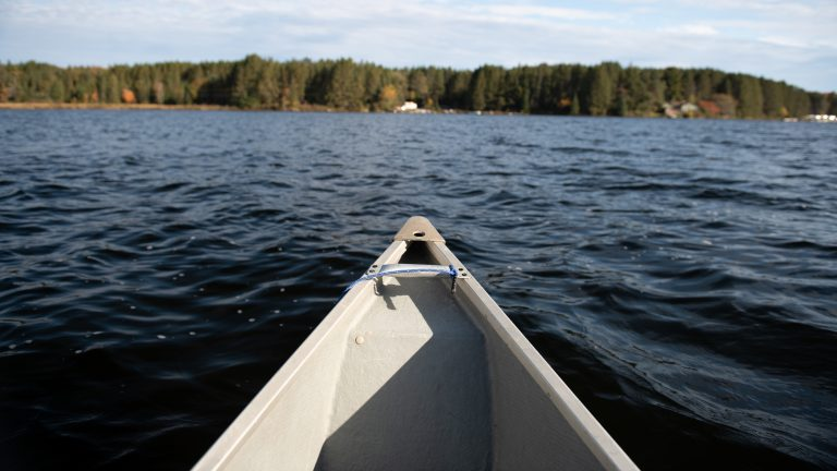 view from inside a canoe of Chache Lake, the shoreline and the front end of a canoe