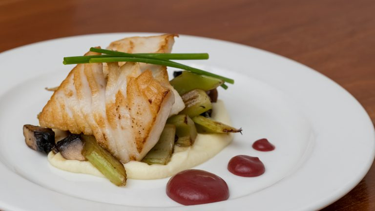 close up of a cod fillet with sauteed vegetables, a creamy vegetable puree and red saud on a white dinner plate