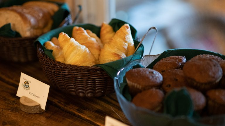 close up baskets of croissants and muffins on a wooden buffet table