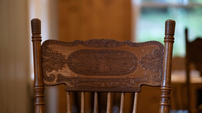 close up of the back of an ornately carved antique wooden dining chair