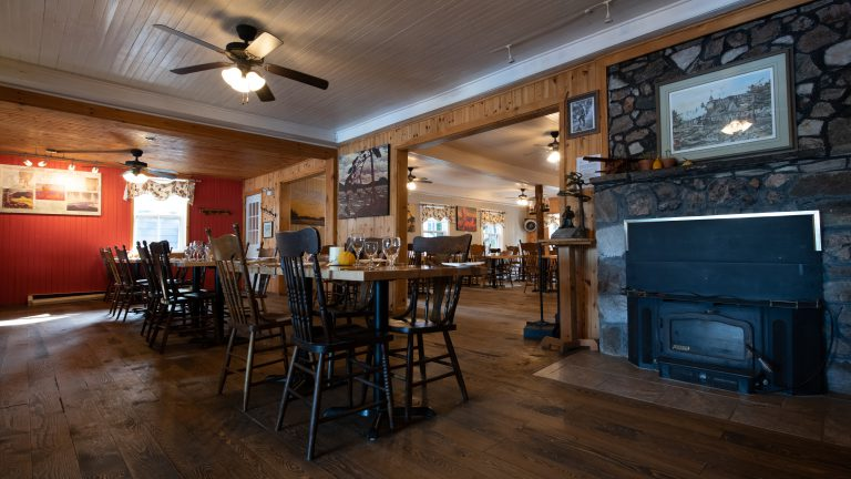 wide shot of rustic dinig room with wood paneled walls, antique furniture and fireplace