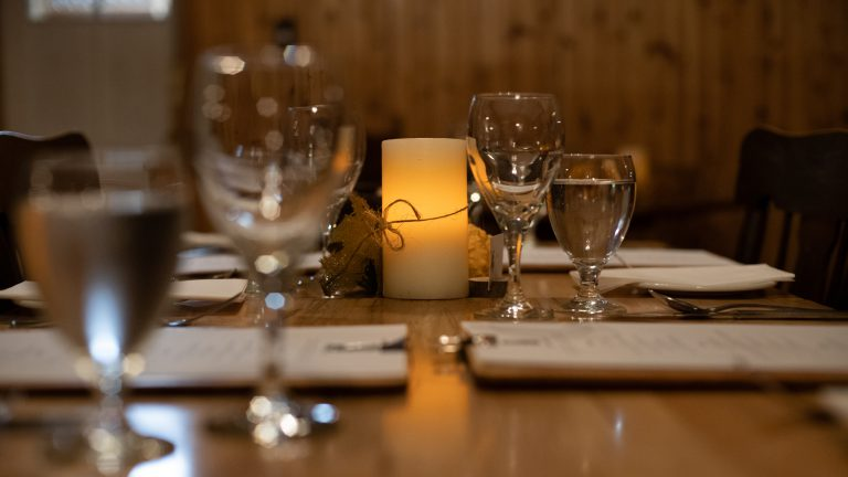 close up of table settings on a long wooden table incluing wine and water glasses, menus and an illuminated candle