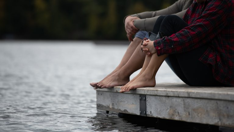 water, the edge of a dock and the lower halves of two people with rolled up pant legs