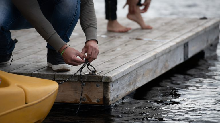 close up of a man's hands tying a yellow kayak to an iron ring on a dock