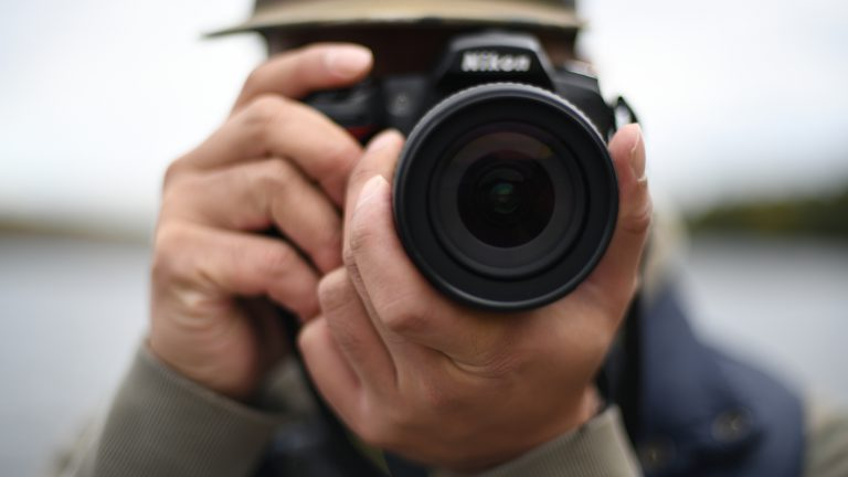 close up of a man wearing a baseball hat holding a camera with large lens up to his face