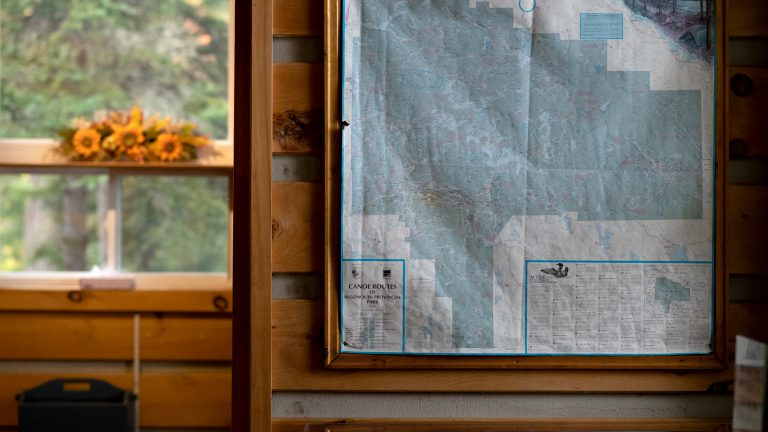 framed antique paper map of Algonquin Provincial Park hanging in rustic cabin