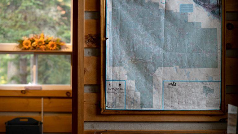 framed antique paper map of Algonquin Provincial Park hanging in rustic cabin
