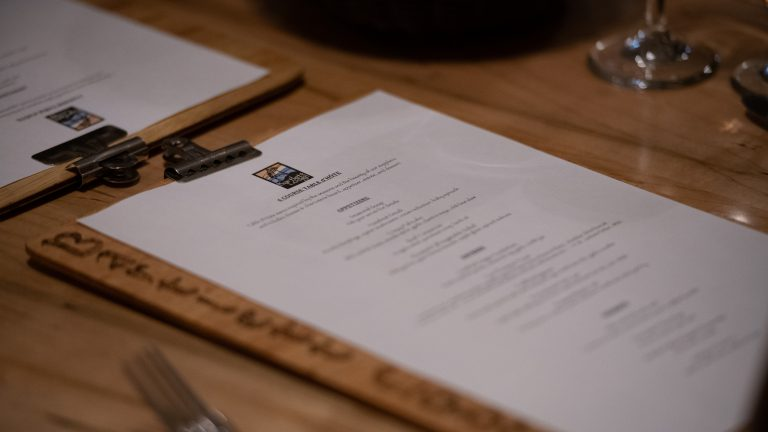 angled close up of paper dining menu on wooden clipboard sitting on a wooden dining table