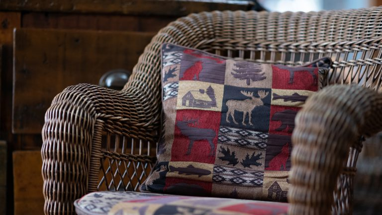 decorative black, red, brown and cream coloured moose pillow sitting on a brown wicker chair