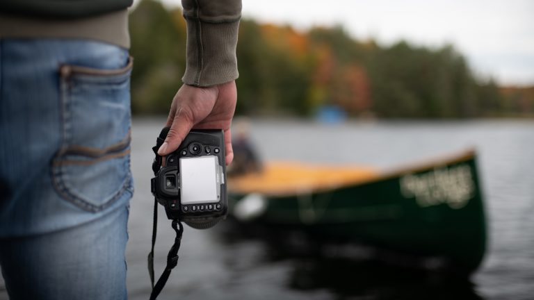 back of a man holding a camera down by his side while standing infront of a canoe in the water