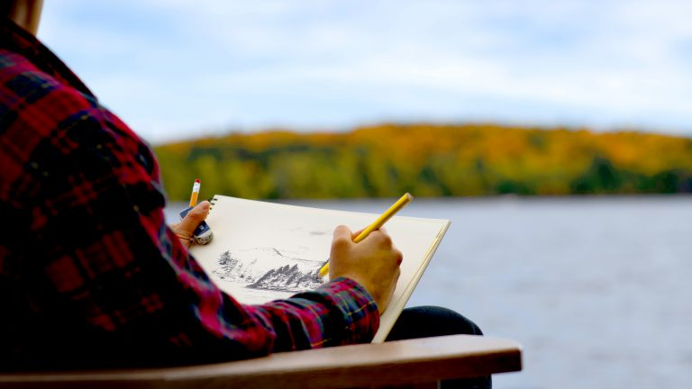 hands of a man wearing plaid sketching a lake and autumn shoreline