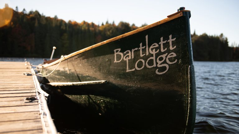 front end of Bartlett Lodge's antique green cedar boat tied to dock