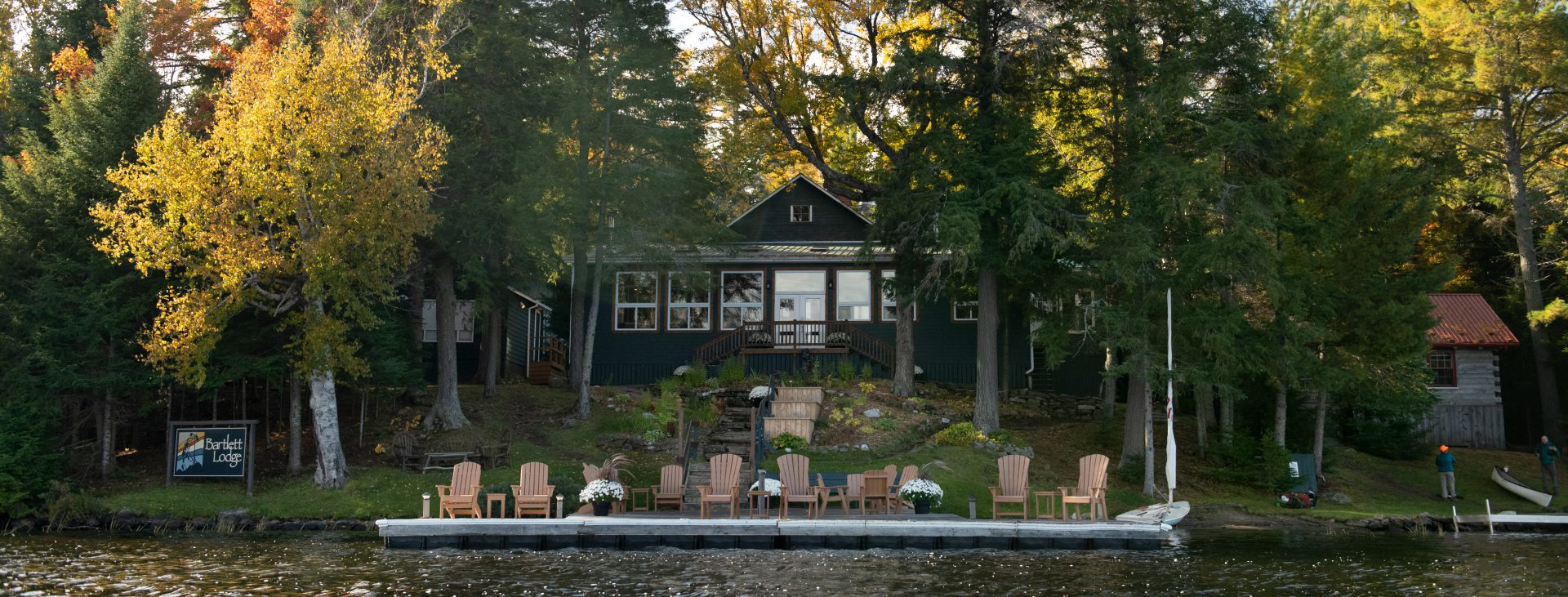 wide shot of the main dining cabin at Bartlett Lodge in the background with a dock and wooden deck chairs in the mid ground and water in the foreground