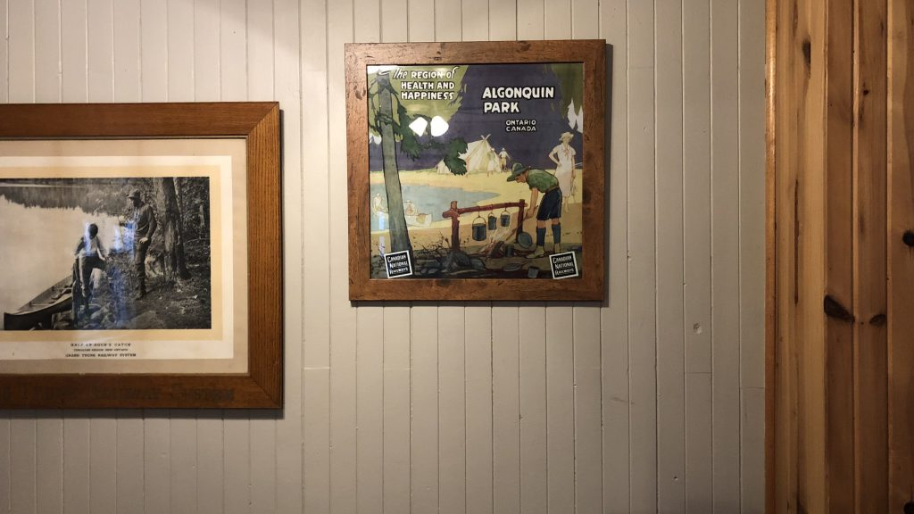 vintage algonquin park poster framed in wood and hanging on a cream coloured wood paneled wall