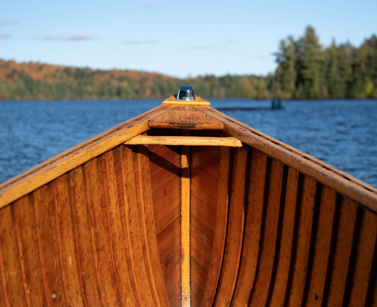 wide view of water taxi taking passengers across a lake with autumn colours visible on the forested shoreline