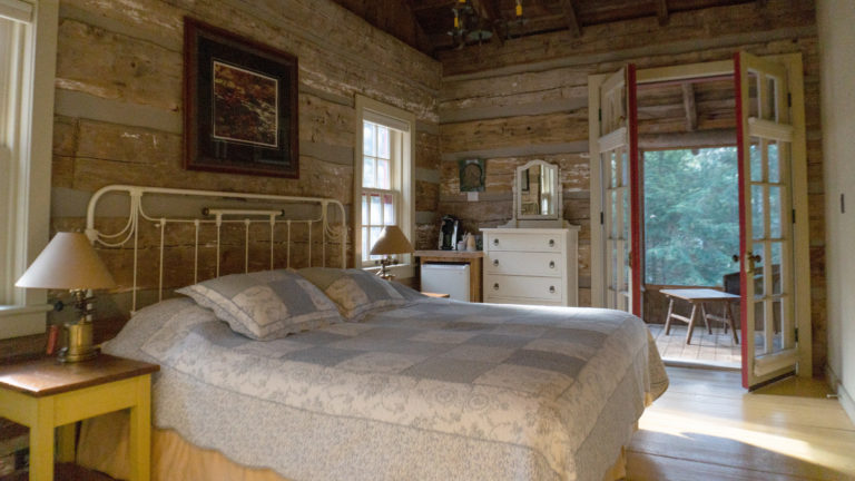 white cast iron bed with blue in white quilt in rustic log cabin room with double french doors openeing on to a screen porch