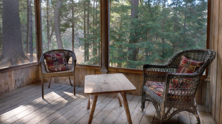 two wicker chairs and a wooden coffee table on a screened in porch surrounded by coniferous trees