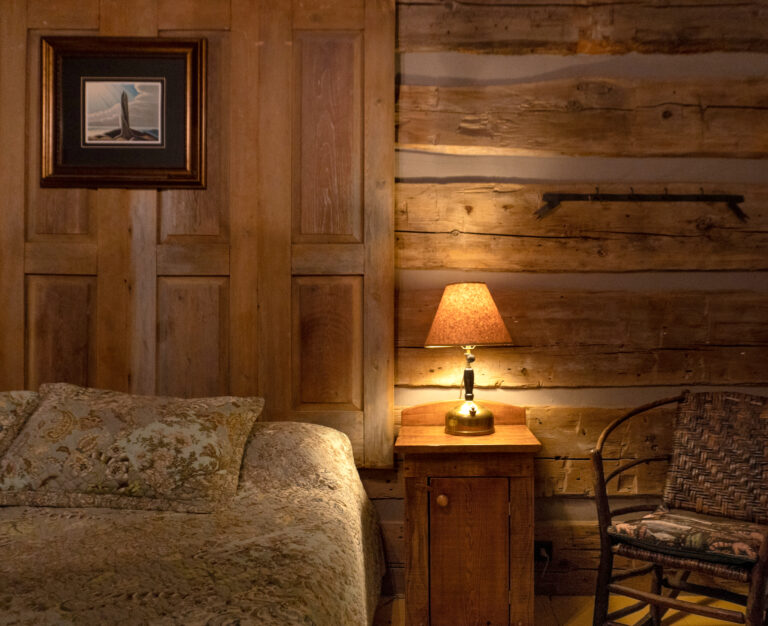interior of a log cabin with bed, wooden nightstand, vintage wood rocking chair and iluminated brass table lamp