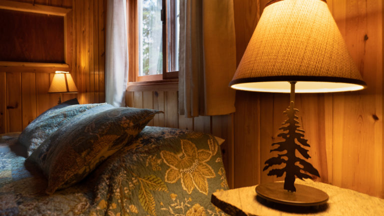 lit bedside table lamp that's shaped like a pine tree inside a wood paneled room beside the pillow of a bed with a blue floral sham