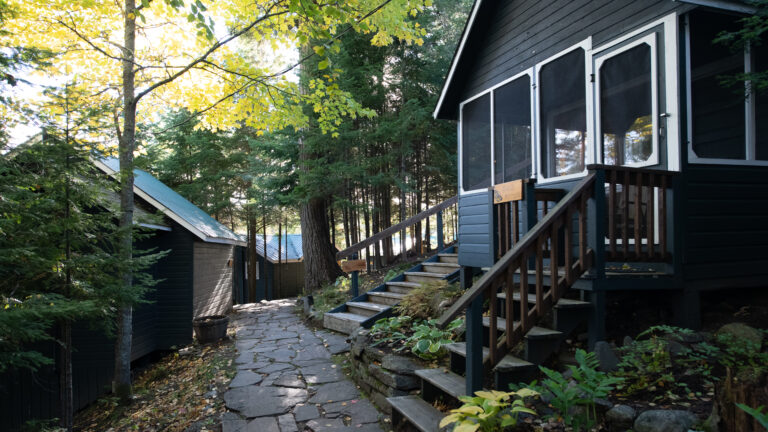 flagstone path leading through the woods with a dark brown cabin on the right and two other cabins further along the path