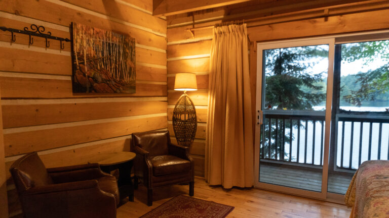 inside a log cabin with two brown leather easy charis, a lit lamp with an antique snowshoe as the base and view of pine trees and a lake through sliding glass doors