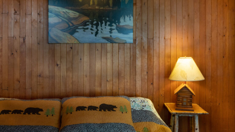 wood-paneled wall with lit bedside table lamp, group of seven artwork and bear-themed pillows