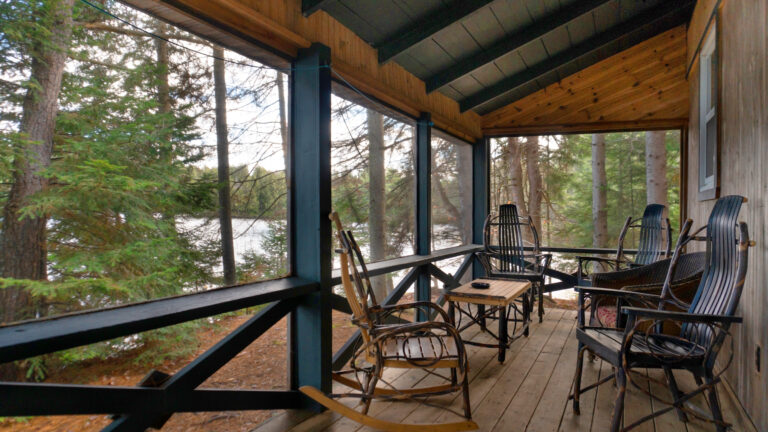 four rustic wooden chairs and a coffee table on a rustic screened porch of a cabin sitting in a coniferous forest with a view of water