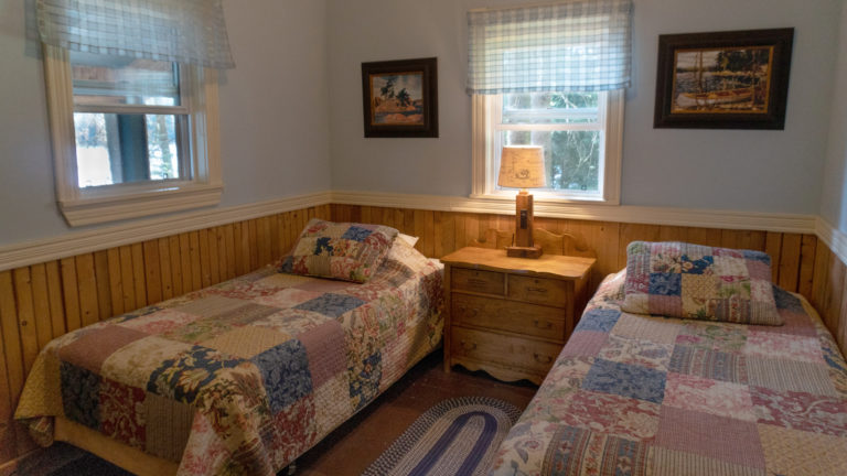 two twin beds covered in patch work quilts seperated by an antique dresser with lamp insude a blue and wood paneled room