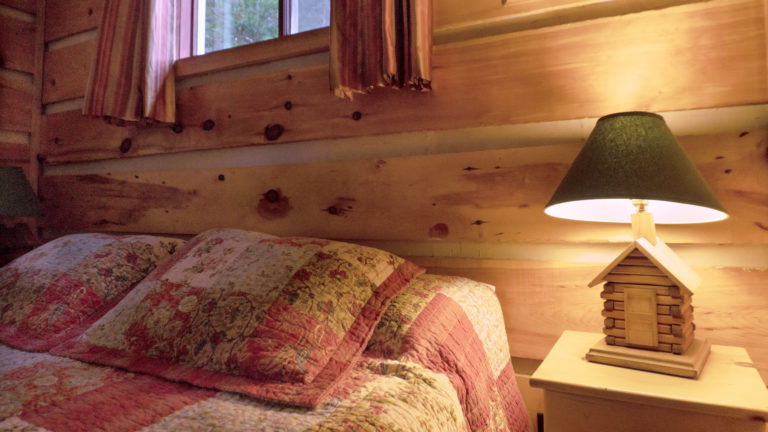 pillows on a bed with pink and white patch work quilt shams in a wood-paneled room with a lit bedside table lamp