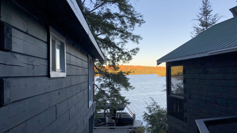 orange fall foliage visibale along the lake's coastline viewed through the space between two cabins