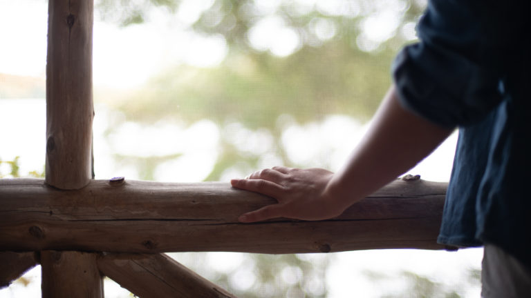 hand resting on the rustic log railing of a screened in porch in the woods overlooking the water