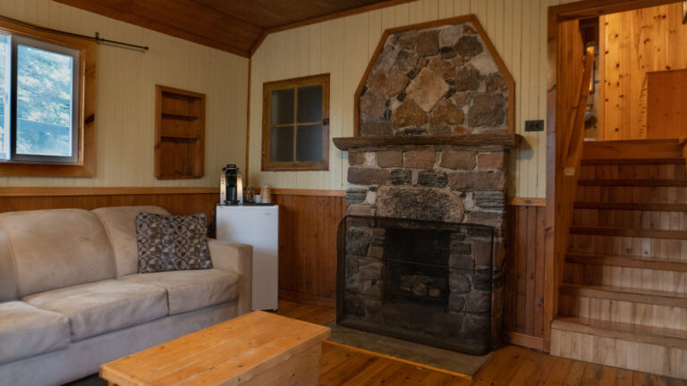 rustic stone firelplace in a wood paneled room with a grey couch, decorative pillow, mini fridge, pine coffee table and view up a staircase