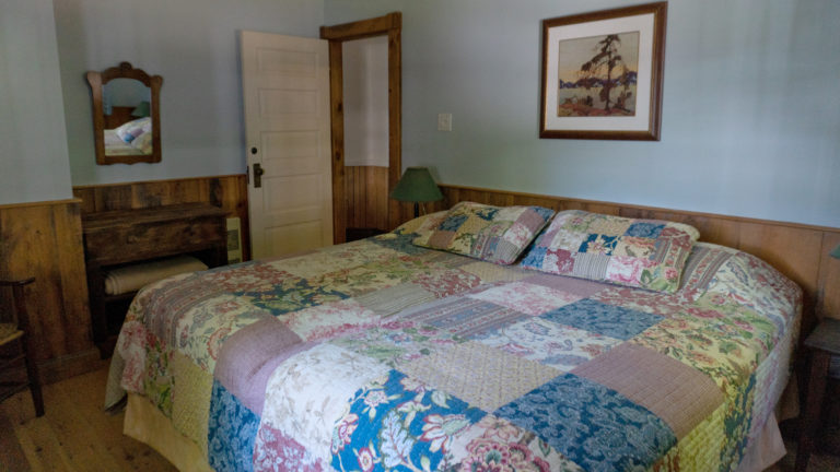 large bed covered in a patch work quilt inside a blue and wood paneled room