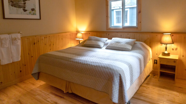 large bed with beige and brown stripped quit in a beige and wood paneld room with two lit bedside lamps