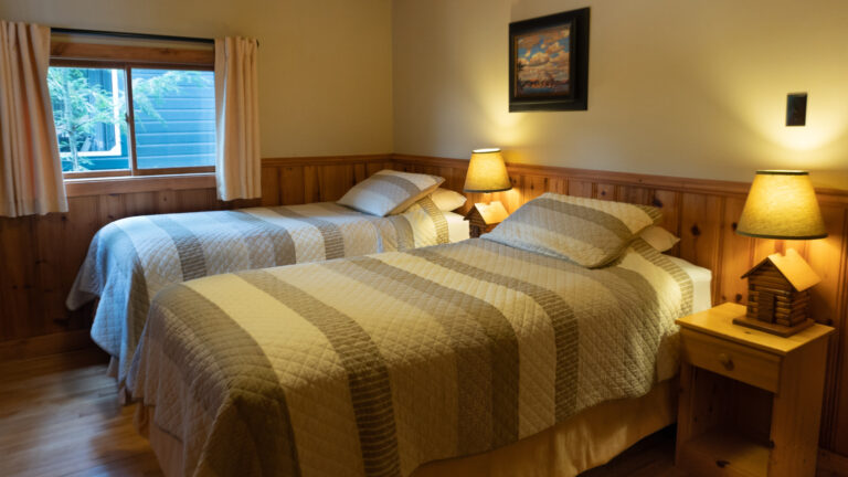 two twin bed with beige and brown stripped quits in a beige and wood paneld room with two lit bedside lamps
