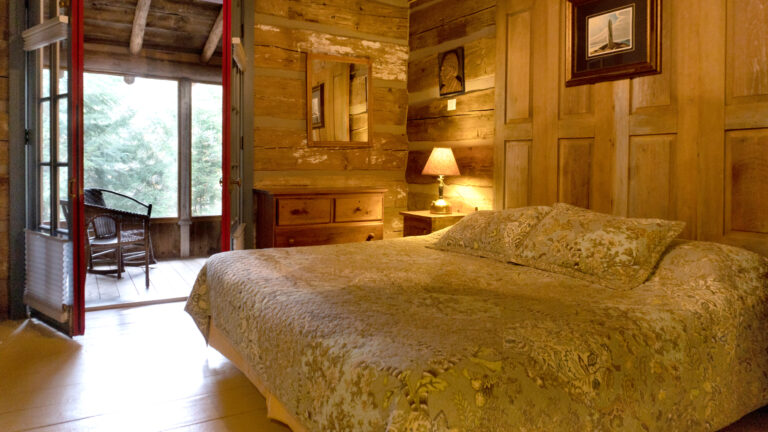 a large bed covered in a sage green floar quilt inside a lamp-lit log cabin roon with a french door opened to a screened in porch