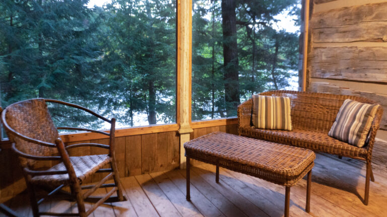 a wicker chair, love seat and table inside a screened in covered porch of a log cabin overlooking a lake and coniferous trees