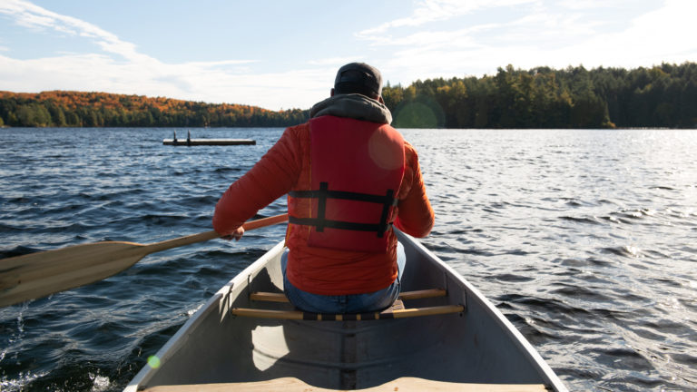 the back of a man paddling a canoe weating an orage coast and life vest with an autumnal-coloured shoreline in the background