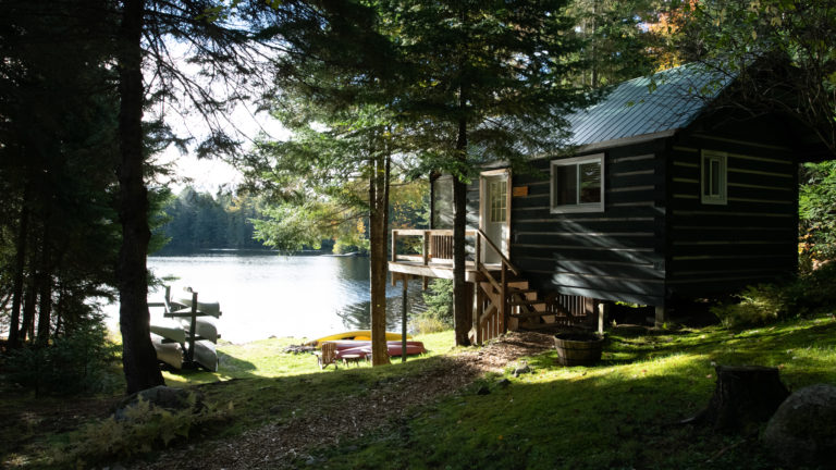 exterior of a log cabin in the woods next to a lake with a canoe rack on the sunny grass