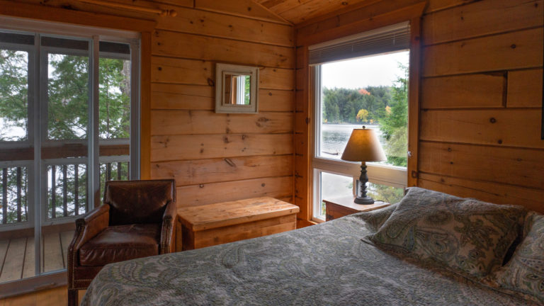 view of a lake through a window in a log cabin