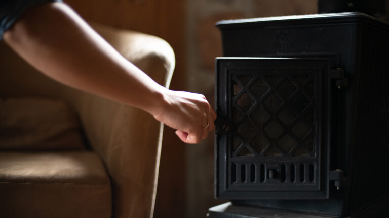 a hand closing the door of a black iron fireplace