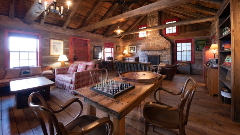 interior of a wood cabin living room with red plaid couches, an antique wooden dining table with a chess board set up, stone fireplace and black iron chandeliers