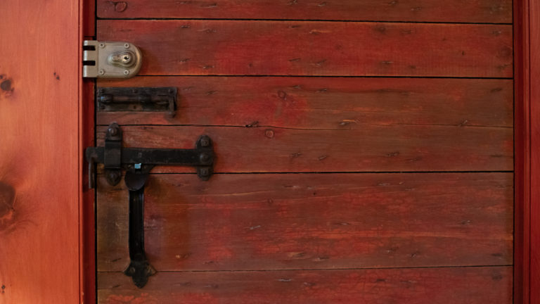 red stained plank wood door with antique black iron hardware