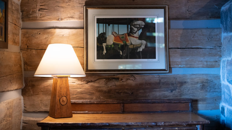 vignette of a rustic wooden illuminated lamp on a live edge wooden surface with a merry go round photograph hanging on the wall of a log cabin