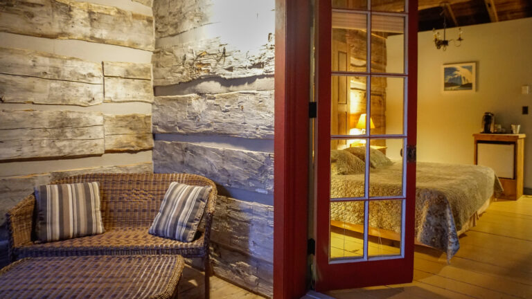 the corner of a log cabin with a wicker love seat outside glass-paneled french doors opening into a bedroom