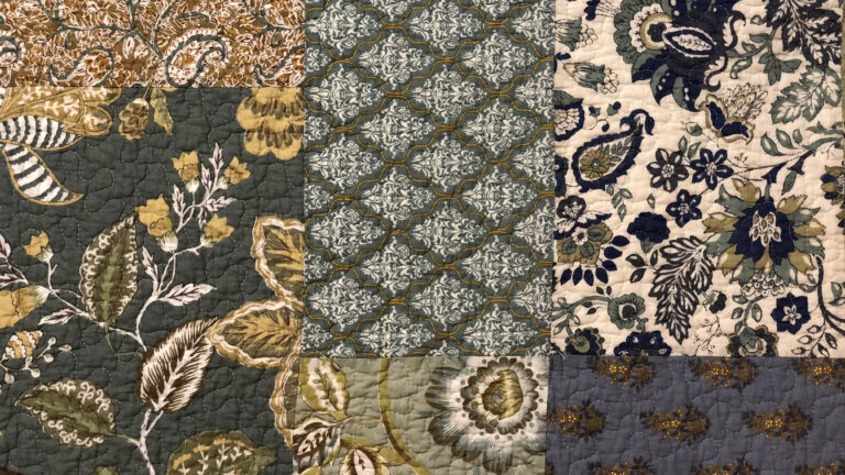 vintage block-pattern quilt with a series of floral patterns in a teal, cream and navy colour palette